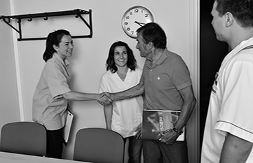 4 personnes sur une photo en noir et blanc. Une femme et un homme se serre la main au centre. Cela représente l'ostéopathe et le patient pour inciter les personnes qui en ont besoin d'aller consulter.