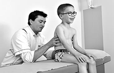 Photo en noir et blanc d'un ostéopathe accroupi derrière un petit garçon à lunettes et qui a ses mains sur son dos. Représentation d'une séance d'ostéopathie pour les enfants