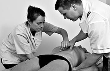 Photo en noir et blanc de deux ostéopathes, une femme à gauche, un homme à droite, qui examine le pléxus d'un patient allongé sur le ventre dont on ne voit pas le visage.